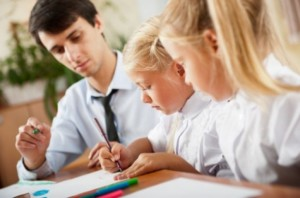 Male teacher helping 2 girls with their work