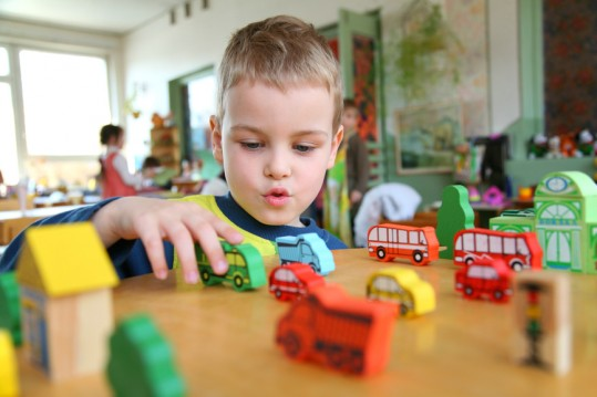boy playing with toy automobile